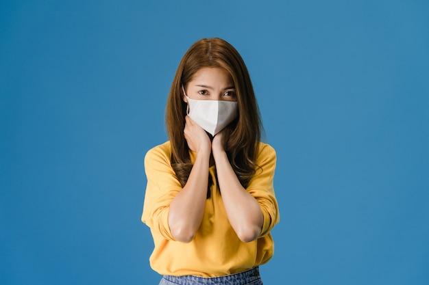 La muchacha joven de asia usa una mascarilla médica, cansada del estrés y la tensión, mira con confianza a la cámara aislada sobre fondo azul. autoaislamiento, distanciamiento social, cuarentena para la prevención del coronavirus.