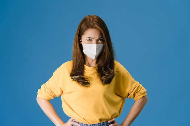 La muchacha joven de asia usa mascarilla médica con expresión negativa, grito emocionado, llorando emocionalmente enojado y mira a cámara aislada sobre fondo azul. distanciamiento social, cuarentena por coronavirus.