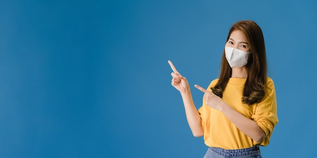 La muchacha joven de asia usa una mascarilla médica que muestra algo en el espacio en blanco con vestida con un paño informal y mira a la cámara. distanciamiento social, cuarentena por coronavirus. bandera panorámica de fondo azul.