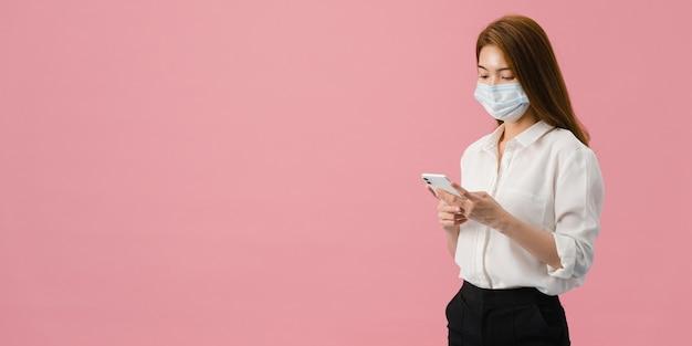 La muchacha joven de asia usa el teléfono móvil con la mascarilla médica vestida con ropa casual.