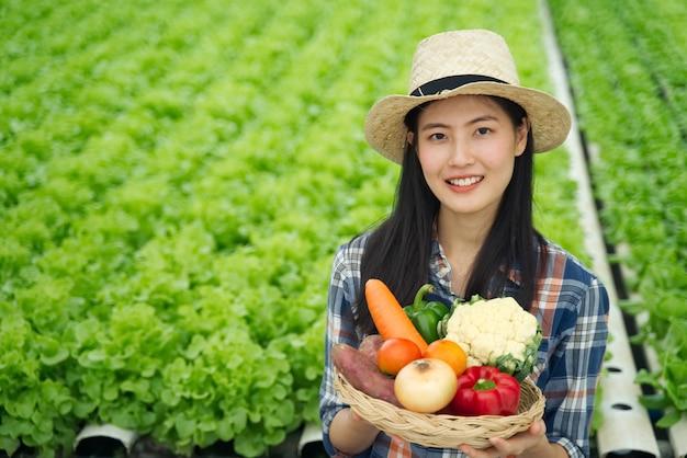 Muchacha joven del granjero que se sostiene diverso de verduras en cesta con sonrisa