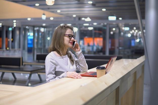 Muchacha joven, hermosa que habla en el teléfono que se coloca en una tabla con un ordenador portátil y una taza de café en el aeropuerto