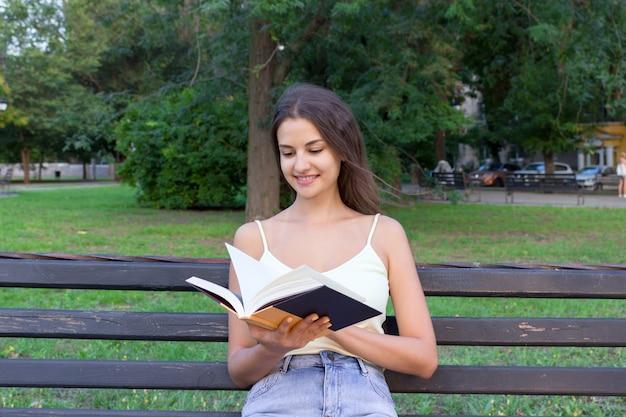 La muchacha linda está buscando la información en un libro de texto que se sienta en el banco en el parque. la mujer está mirando a través de un libro y buscando algo interesante.
