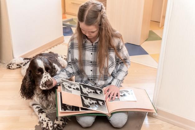 Muchacha linda joven que mira el álbum de foto con su perro en casa en piso.
