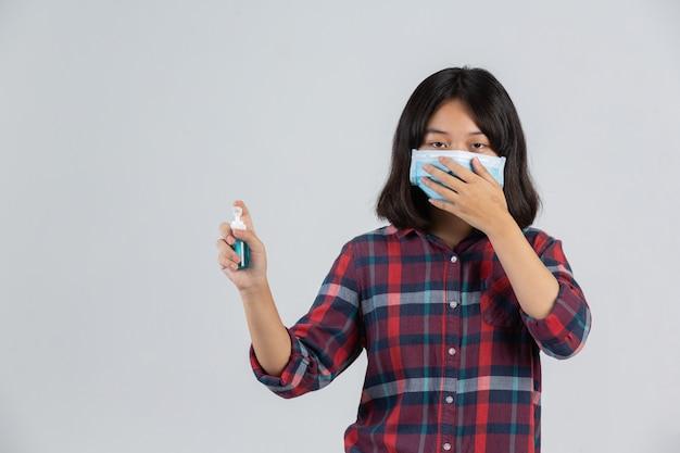 La muchacha linda lleva la máscara y está sosteniendo el gel de las manos mientras que se coloca en la pared blanca