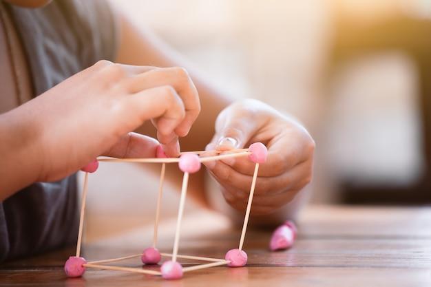 Muchacha linda del niño asiático que juega y que crea con la pasta del juego y el toothpick.