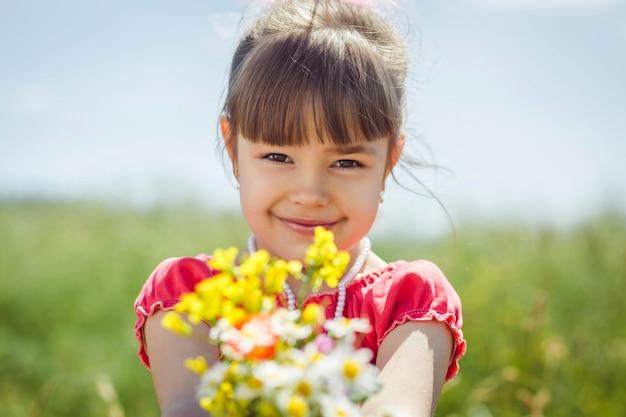Muchacha linda del niño con las flores