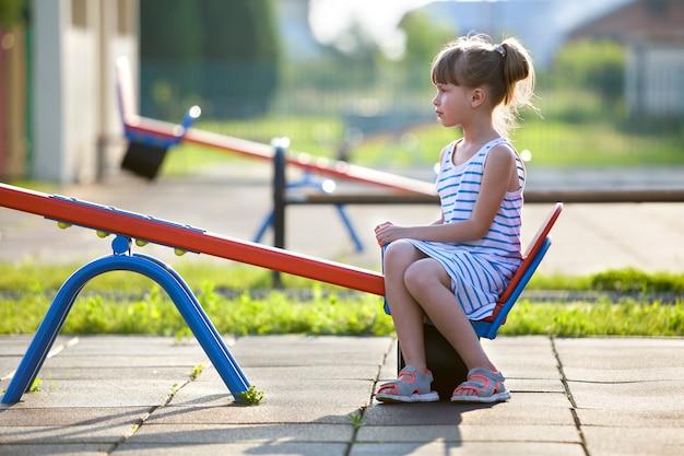 Muchacha linda del niño joven al aire libre en el oscilación del balancín en día de verano soleado.