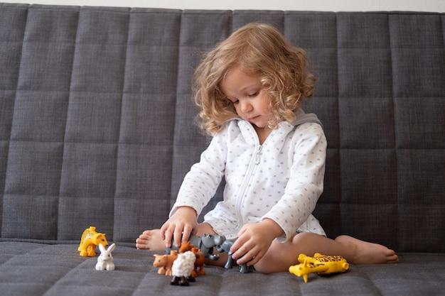 Muchacha linda del niño que juega con el zoológico de juguete que se sienta en el sofá. niño con juguete educativo. desarrollo temprano