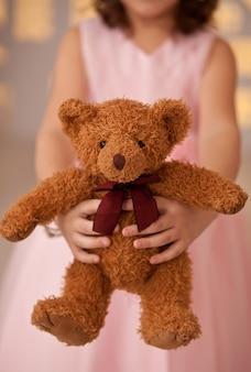 Muchacha linda que sostiene un pequeño oso de peluche marrón del juguete en manos.
