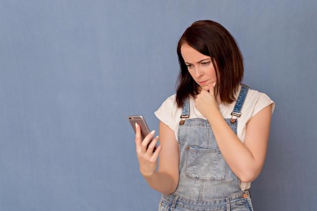 La muchacha mira cuidadosamente el teléfono en un fondo azul.