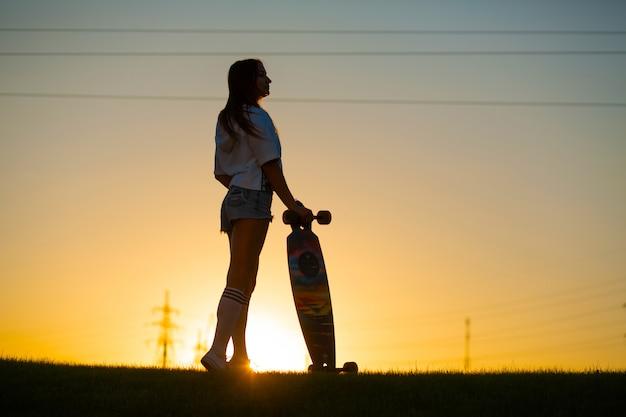 La muchacha mira la puesta del sol que sostiene un longboard en su mano