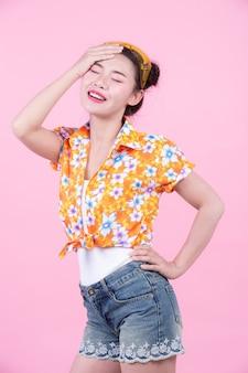 La muchacha de la moda se viste para arriba con gestos de mano en un fondo rosado.