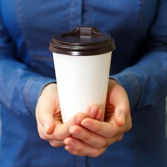 La muchacha modelo joven de las manos en camisa del dril de algodón sostiene el vidrio plástico de papel del café que bebe