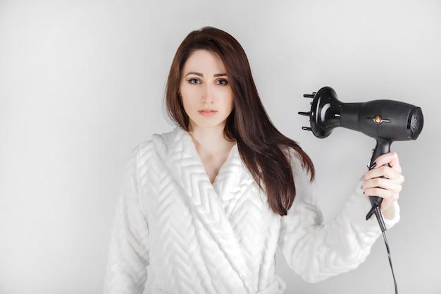 La muchacha morena en albornoz con el secador de pelo se seca el pelo contra un fondo blanco.