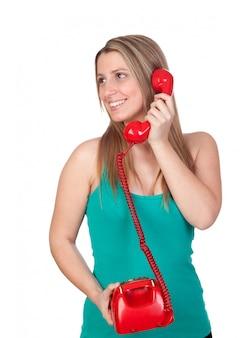 Muchacha morena atractiva que llama con el teléfono rojo aislado en el fondo blanco