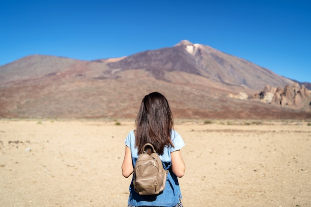Muchacha morena bonita que camina al aire libre cerca del volcán del teide en la isla de tenerife.
