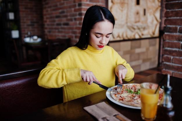 Muchacha morena divertida en suéter amarillo que come la pizza en el restaurante.