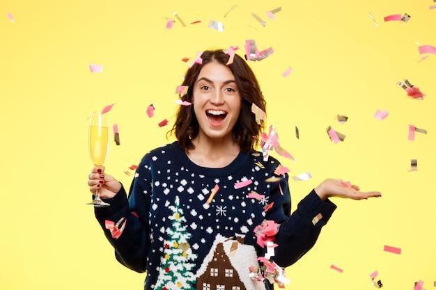 Muchacha morena hermosa alegre joven en suéter hecho punto acogedor que sonríe sosteniendo la copa de champán sobre fondo amarillo con confeti que cae.