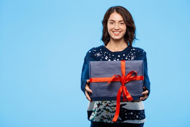 Muchacha morena hermosa joven en suéter hecho punto acogedor que sonríe sosteniendo la caja de regalo sobre fondo azul.