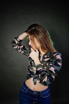 La muchacha morena hermosa lleva la camisa militar y los vaqueros, presentando en el estudio contra fondo gris.