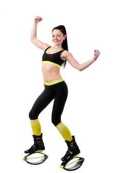 La muchacha morena sonriente en kangoo salta los zapatos que muestran músculos en sus manos.