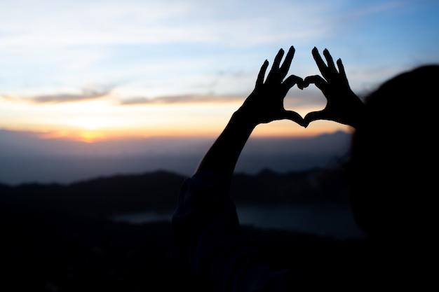 La muchacha muestra el corazón con las manos. sobre el volcán batur. bali. indonesia