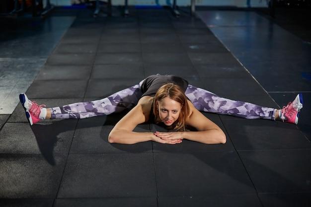 Muchacha muscular hermosa en las polainas grises que hacen estirar. pabellón deportivo en estilo industrial.
