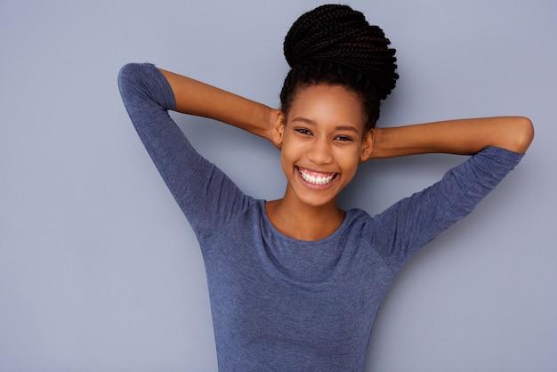 Muchacha negra joven alegre con las manos detrás de la cabeza que sonríe en fondo gris