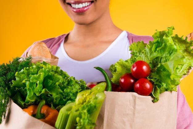La muchacha negra sonríe y sostiene verduras.