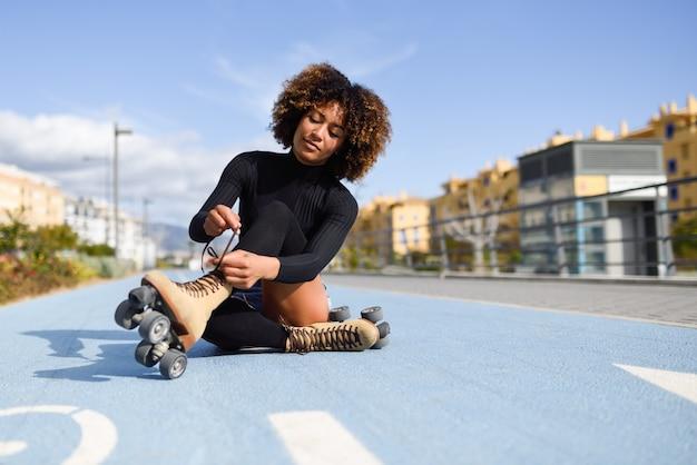 La muchacha negra sonriente de los jóvenes que se sienta en la línea de la bici y pone patines.