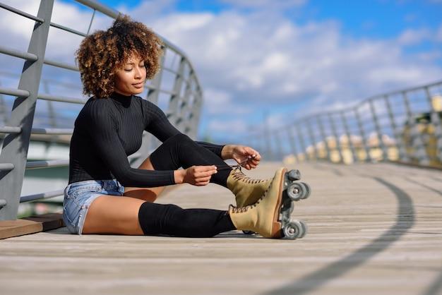 La muchacha negra sonriente de los jóvenes que se sienta en el puente urbano y pone patines.