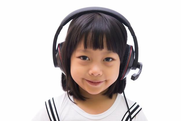 Muchacha del niño con los auriculares en la cabeza aislada en el fondo blanco.