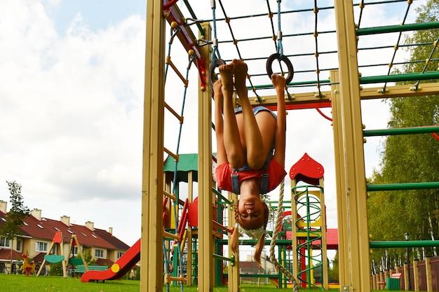 Muchacha del niño colgado boca abajo en el patio de recreo. niña adolescente sonriente jugando en una construcción deportiva.