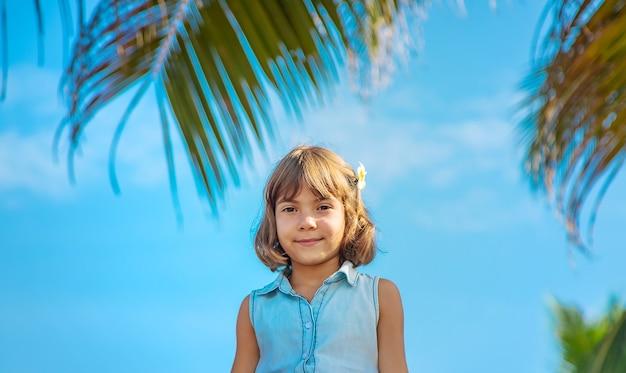 Muchacha del niño en el fondo de palmeras y océano. enfoque selectivo.