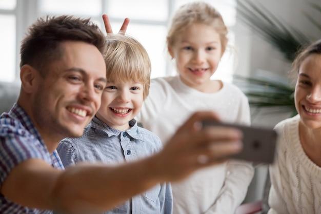 Muchacha del niño haciendo orejas de conejo hermano mientras el padre toma selfie
