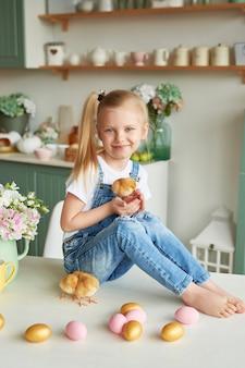 Muchacha del niño con los huevos de pascua y pollos en cocina. feliz concepto de pascua. familia feliz preparándose para la pascua.