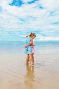 Muchacha del niño en la playa en el océano. enfoque selectivo.