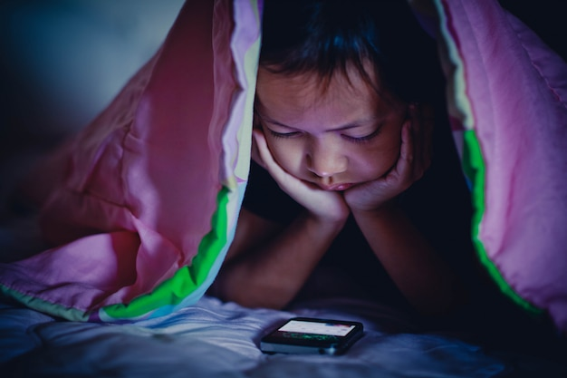 Muchacha del niño que mira smartphone en oscuridad debajo de la manta