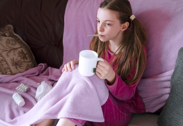 Muchacha del niño que se sienta en cama con el termómetro en boca debajo de la manta y que bebe té