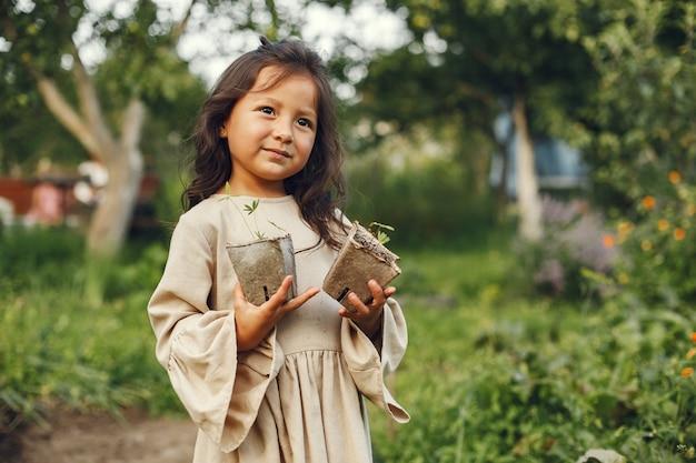 Muchacha del niño que sostiene una plántula lista para ser plantada en el suelo. jardinero pequeño con un vestido marrón.