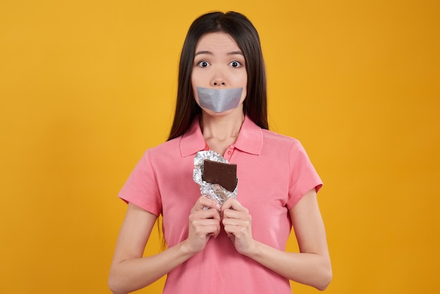 La muchacha no puede comer el chocolate aislado en amarillo.
