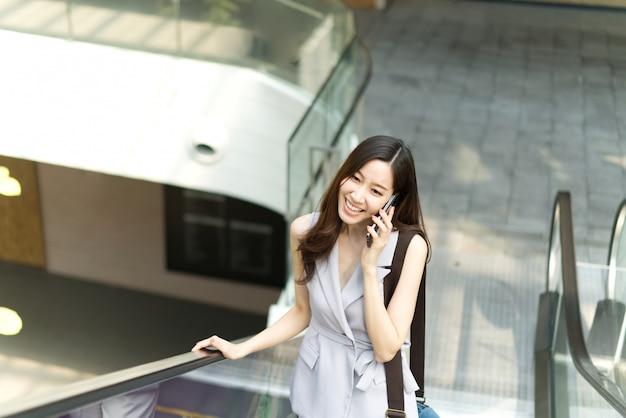 Muchacha de oficina asiática que habla en el teléfono móvil que se coloca en el elevador en alameda de compras.