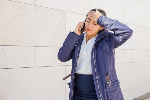 Muchacha de oficina cansada que habla en el teléfono móvil