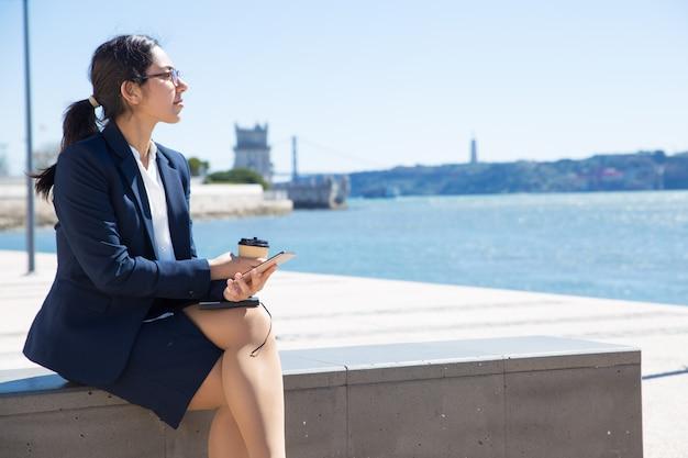 Muchacha de oficina pensativa que disfruta de las vacaciones de trabajo