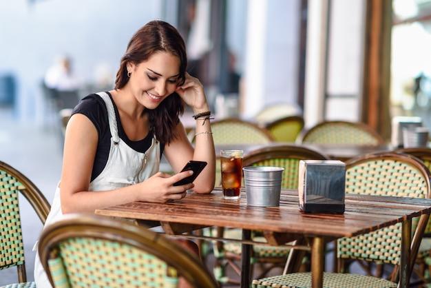 Muchacha con los ojos azules que se sientan en el café urbano usando la sonrisa del teléfono elegante
