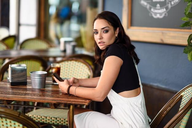 Muchacha con los ojos azules que se sientan en el café urbano usando el teléfono elegante