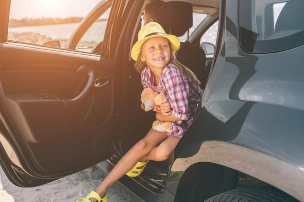 Muchacha con el oso de peluche listo para el viaje para las vacaciones de verano.