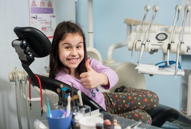 Muchacha paciente feliz que muestra los pulgares para arriba en el consultorio dental.