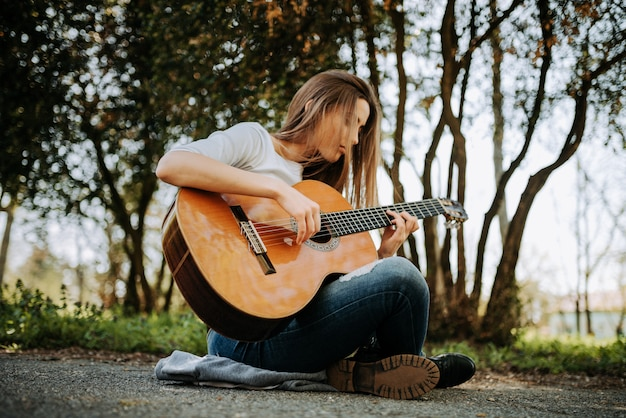 Muchacha pacífica joven que toca la guitarra acústica en el parque.